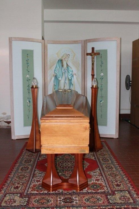 una bara in legno sorretta da 4 paletti rossi e davanti un cartellone con la figura della Madonna e una croce