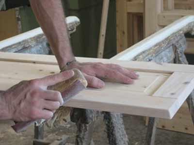 artigiano a lavoro mentre scartavetra una porta