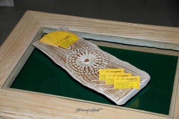 Un cornice di legno e un pezzo di legno con un fiore cesellata