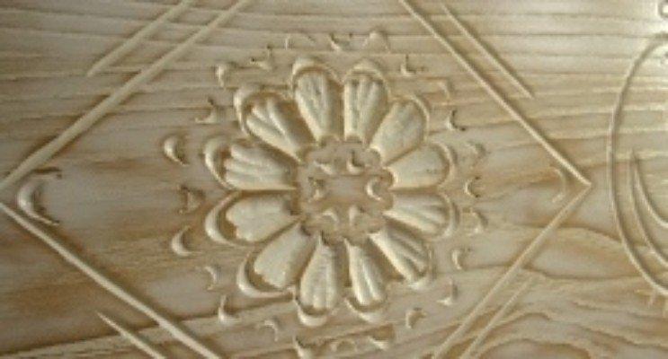 Primo piano di una porta vecchia con un fiore cesellata in legno