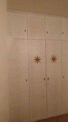 Grande armadio di legno di quattro porte con due stelle sulle porte centrali