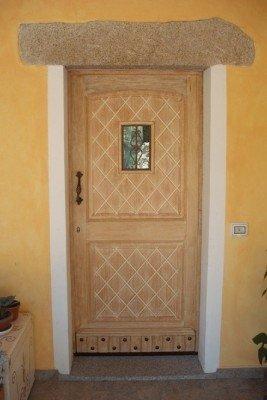 Porta di legno cesellata con disegno di rombi e rafforzamento di chiodi nella parte bassa