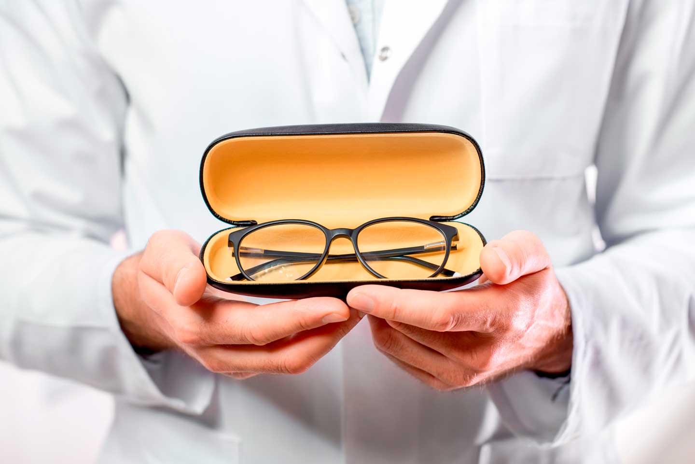 Un ottico che mostra occhiali da vista con montatura nera