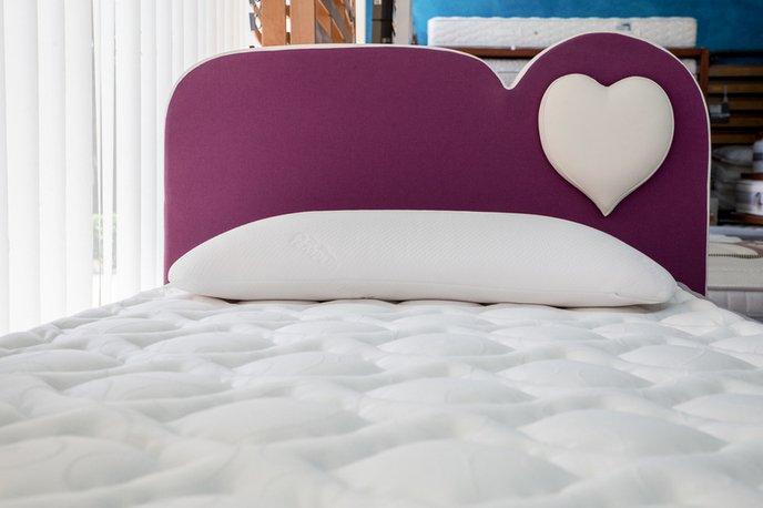 un letto con la spalliera a sagomata e un cuore
