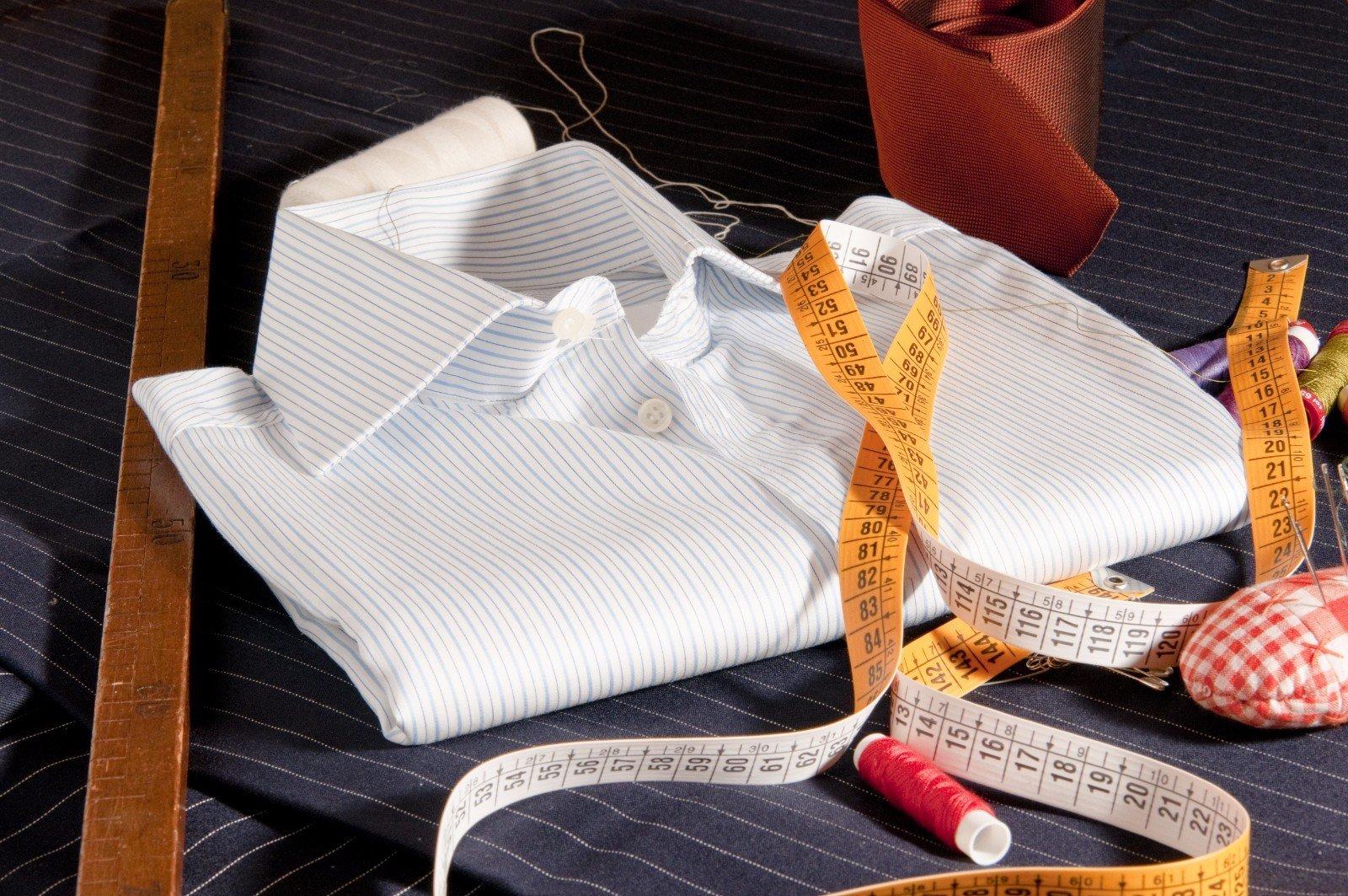 Una camicia piegata insieme a un metro di legno ,altro normale,varie bobine di filo e aghi