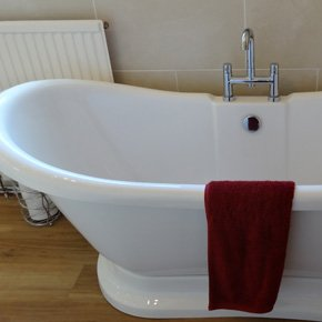 White freestanding bath with red towel on the side