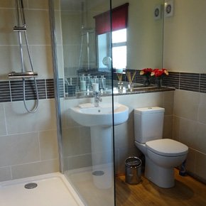 White bathroom suite with a walk in shower