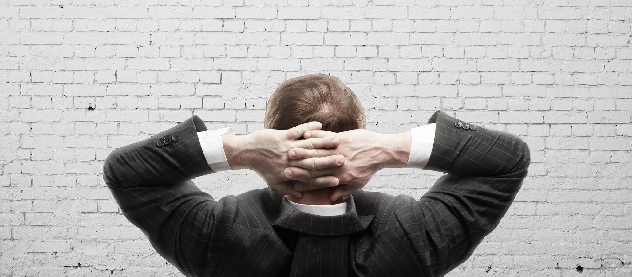 man looking at a blank brick wall