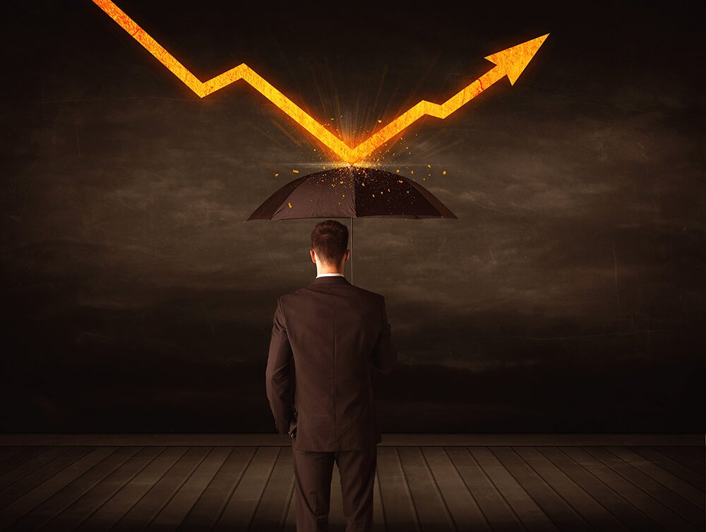 businessman with an umbrella deflecting a drop in profit