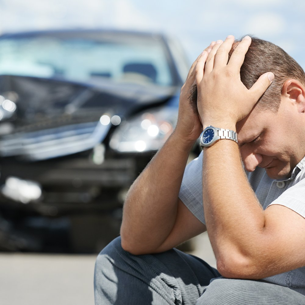 A man upset over his wrecked car after an accident
