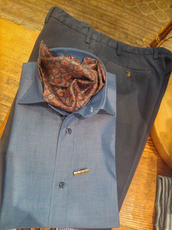 una camicia azzurra e un paio di pantaloni grigio scuro