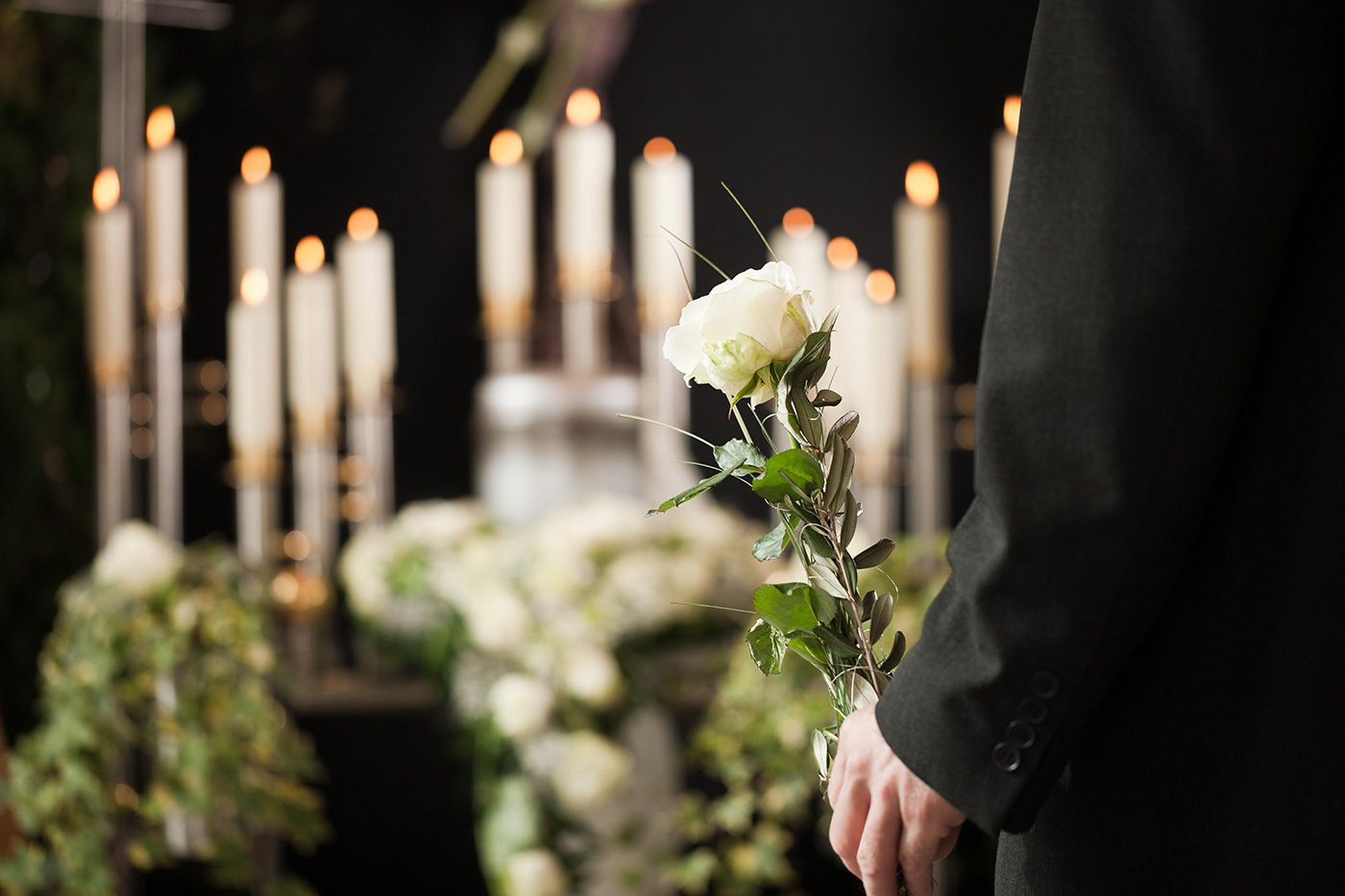 Uomo che tiene un fiore bianco in chiesa
