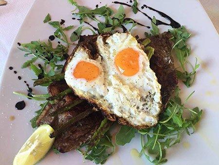 un piatto di bistecca ai ferri con uovo all'occhio di bue