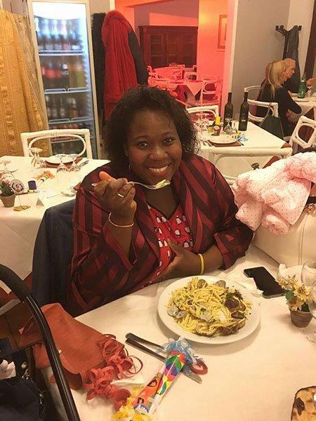 una donna che mangia spaghetti alle vongole in un ristorante