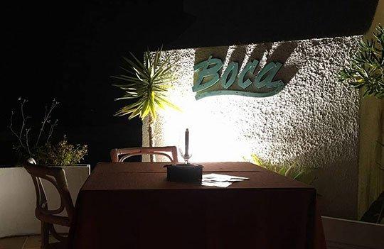 un tavolo da due e una insegna del ristorante Boca al muro