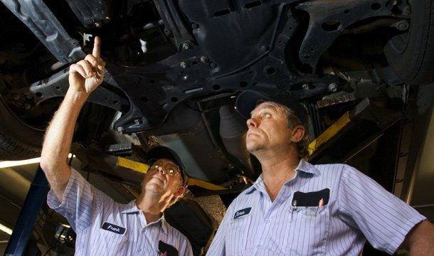 a b truck rentals mechanics under car on lift