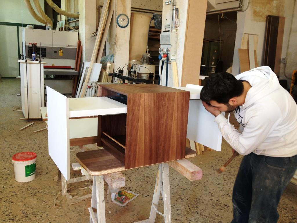 mobile in legno con cassetti ambo i lati e ante bianche mentre un ragazzo apre un cassetto