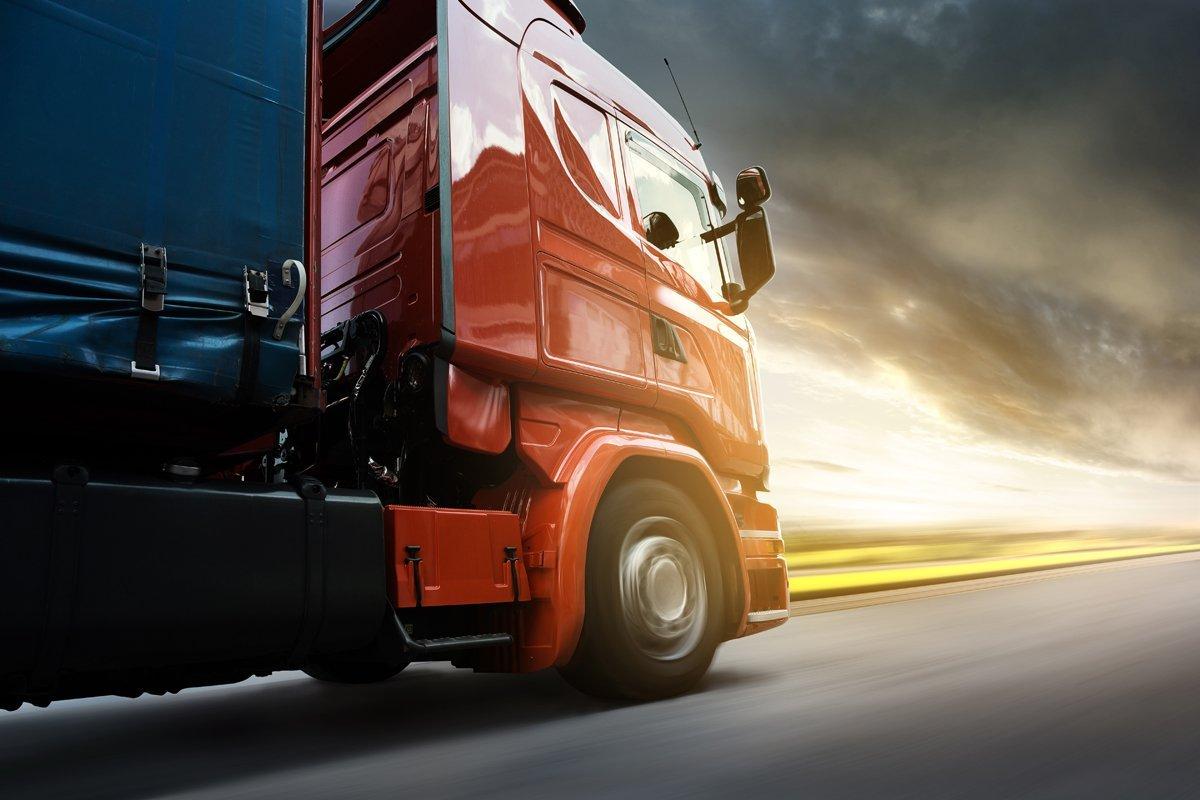 vista laterale di un camion rosso durante l'alta velocità sulla strada
