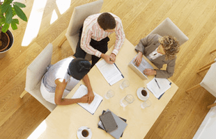 Three people having a meeting around a table