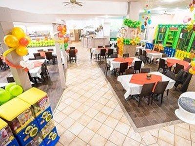 interno di un ristorante con tavoli apparecchiati con tovaglie bianche e tovagliette rosse e dei palloncini a forma di fiore