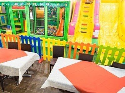 dei tavoli apparecchiati e dietro uno steccato colorato con degli scivoli di gomma colorati