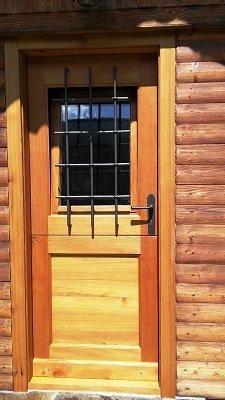 una porta in legno con una piccola griglia di ferro