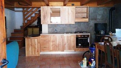 una cucina monoblocco con armadi in legno