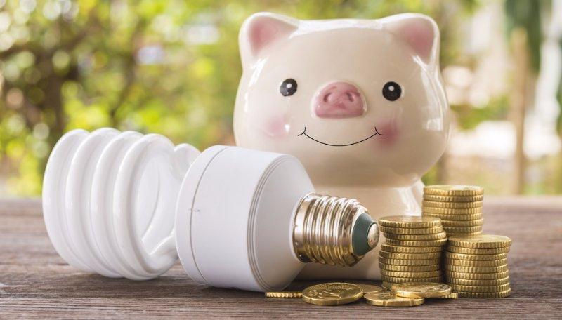 Una lampadina, un salvadanaio e delle monete