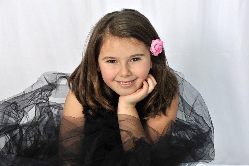 bambina in posa per una foto con rosa nei capelli