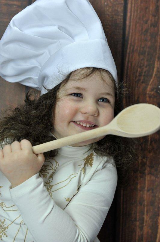 bambina con cappello da chef e cucchiaio di legno in mano