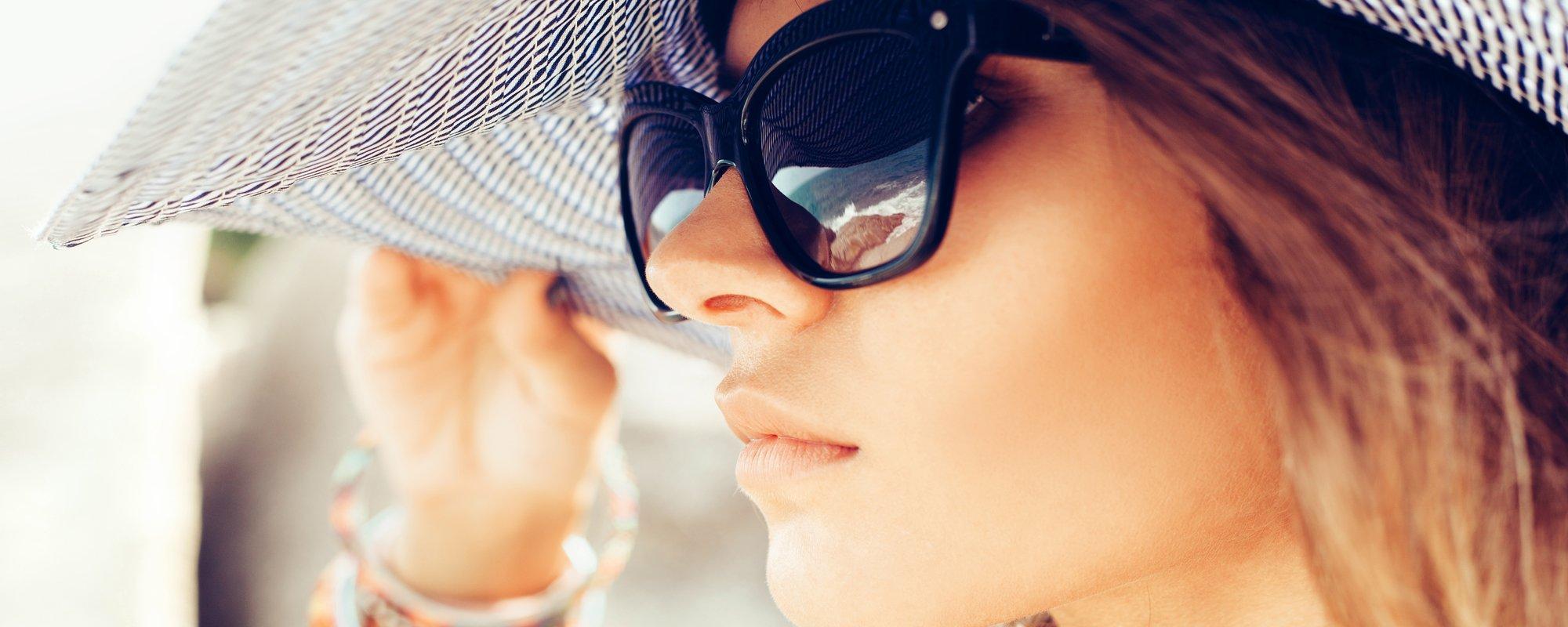 modella con cappello indossa un paio di occhiali da sole e guarda il mare all`orizzonte