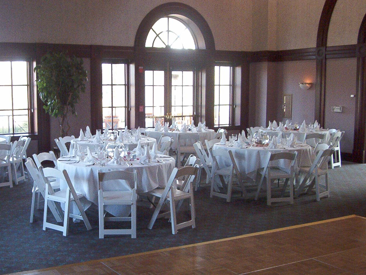 Setup featuring wine glasses, linens and padded chairs
