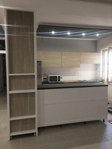 una cucina con dei mobiletti e un mobile bianco con delle mensole
