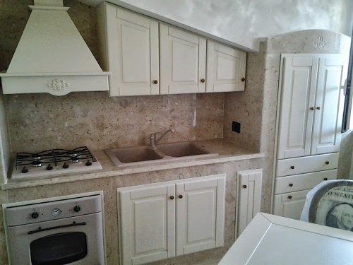 una cucina con mobili bianchi