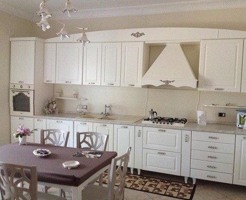 una cucina con mobili in legno di  color bianco e un tavolo con delle sedie