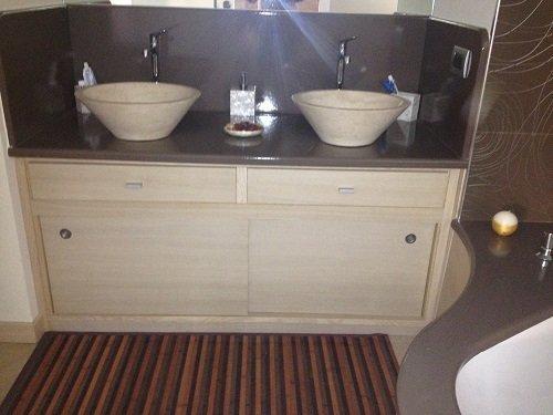un mobiletto in legno sotto a due lavabi