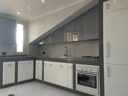 una cucina angolare con mobili bianchi e grigi