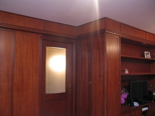 un mobile con una tv, una parete e una porta in legno
