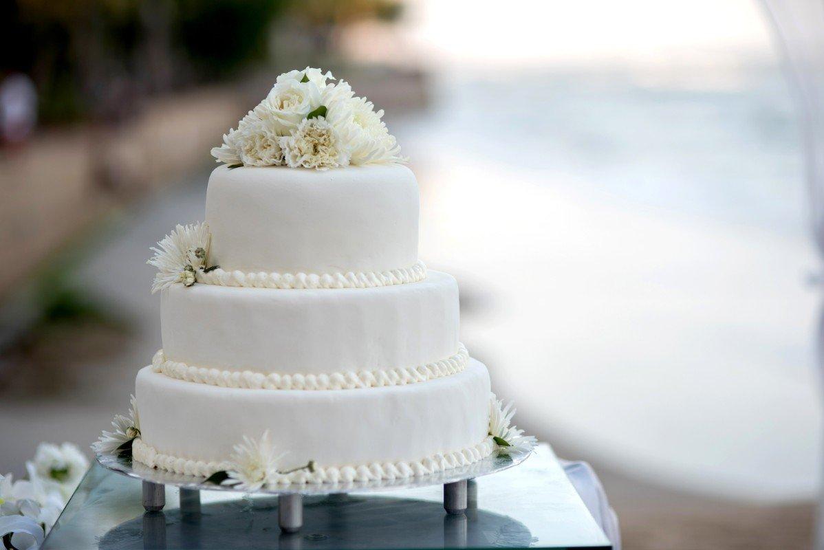 Torta nuziale di tre piani e decorazioni floreali bianchi