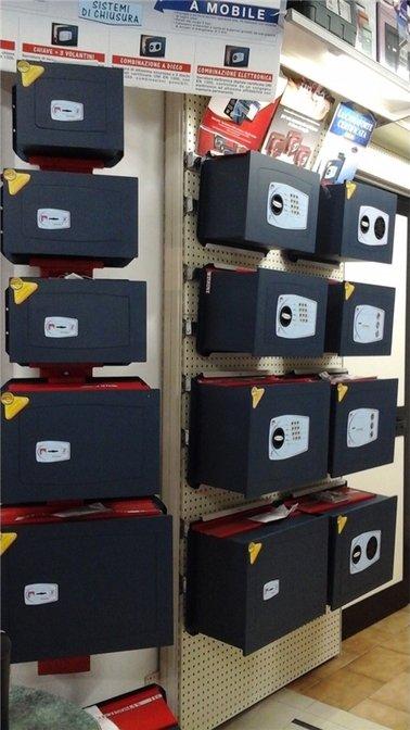 delle cassaforti in acciaio di color nero esposte su dei pannelli a muro all'interno di un negozio di ferramenta