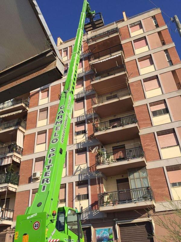 Elevatore per traslochi di color verde davanti a un condominio
