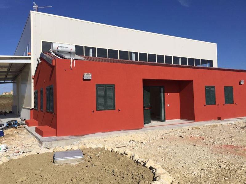 un'industria vista dall'esterno di color rosso e la parte piu' alta di colore bianco