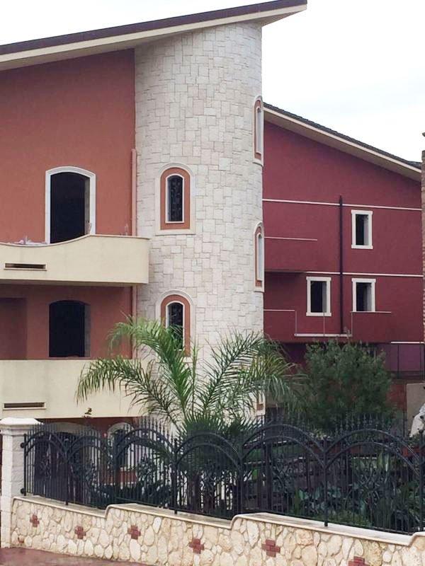 una casa con facciata bordeaux e marrone con una ringhiera nera in ferro e degli alberi