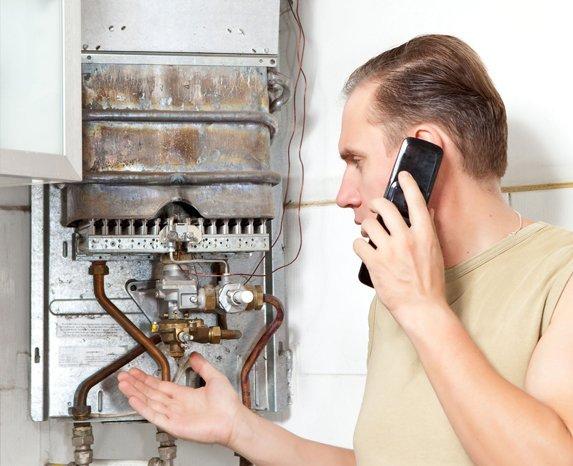 Man on phone checking boiler