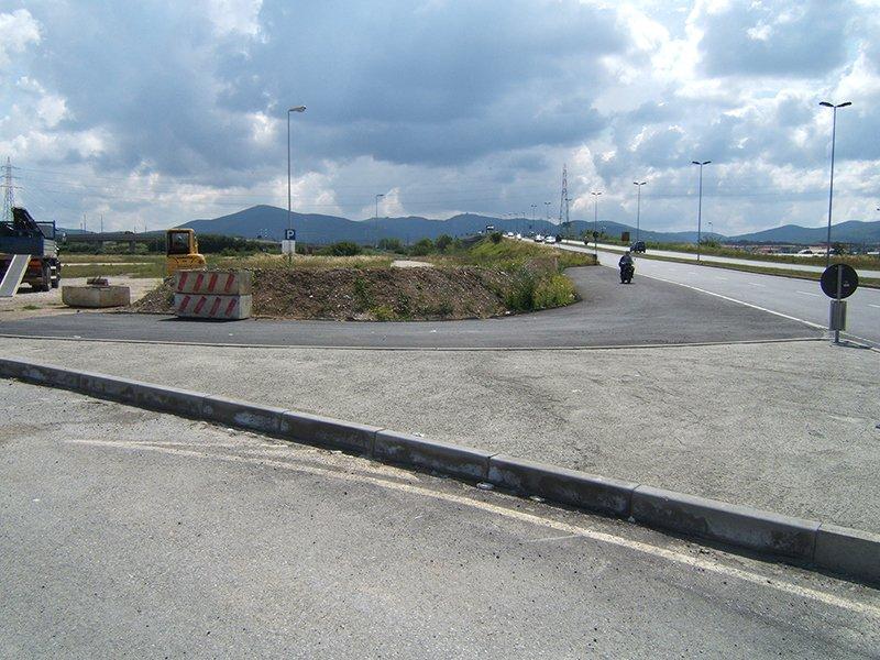 un'isola stradale, un cantiere e vista in lontananza delle montagne