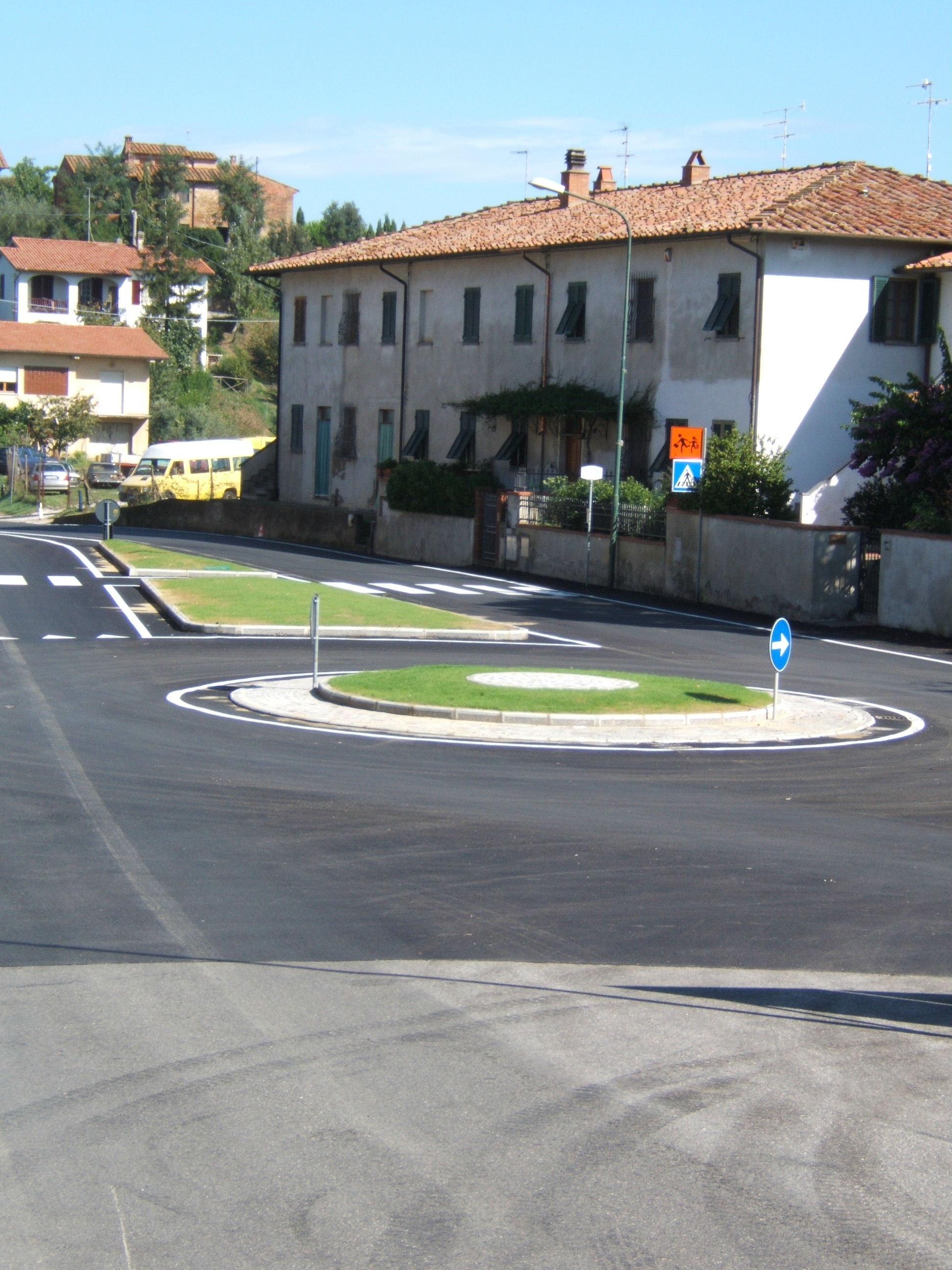 una strada con una rotonda con in mezzo dell'erba e dietro una casa