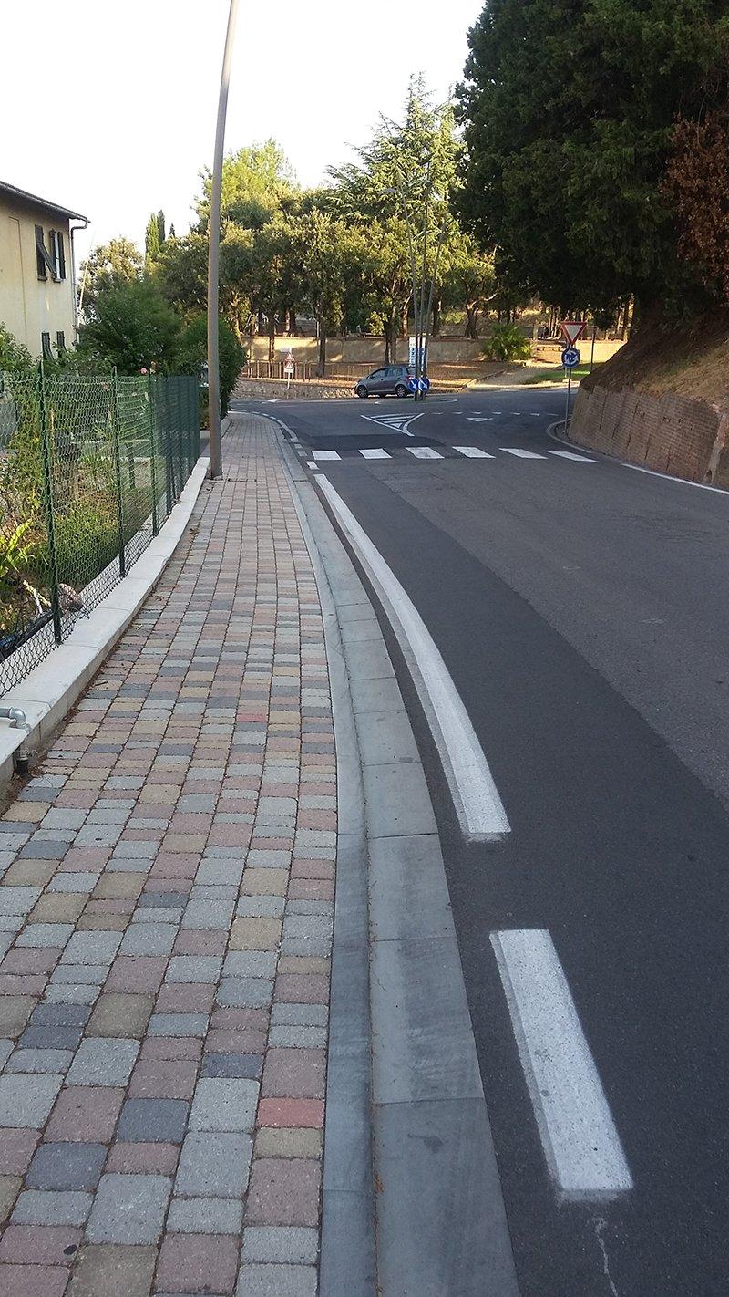 vista di una strada rifatta con un marciapiede e sulla sinistra una recinzione verde