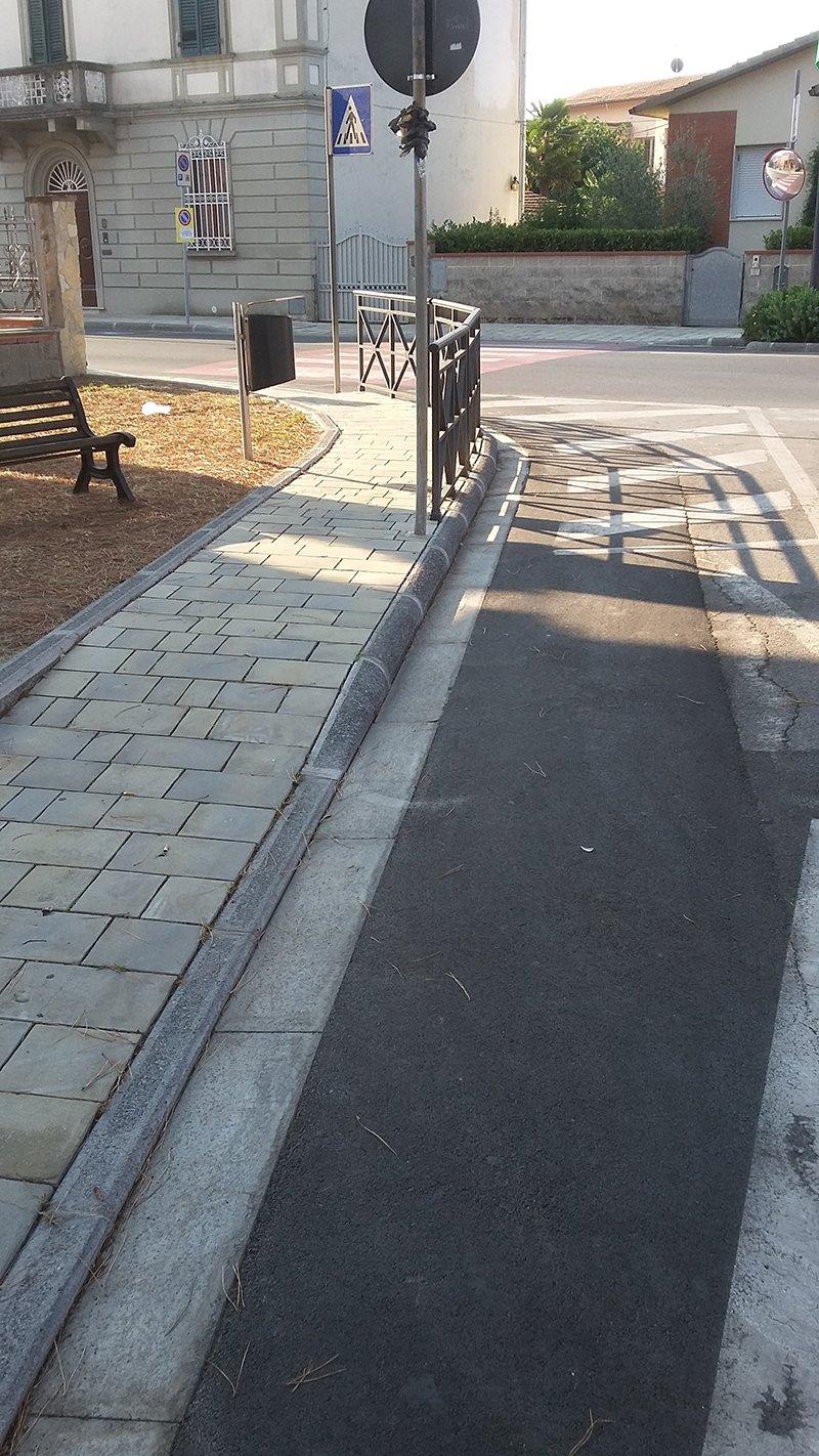 vista di un marciapiede in una strada e sulla sinistra una piazzetta con una panchina di legno