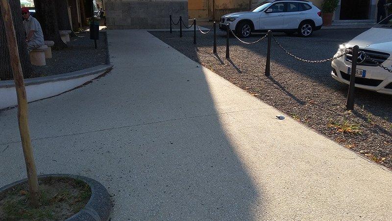 una pavimentazione sulla sinistra una piccola aiuola con un albero e sulla destra dei paletti con delle catene e delle macchine parcheggiate