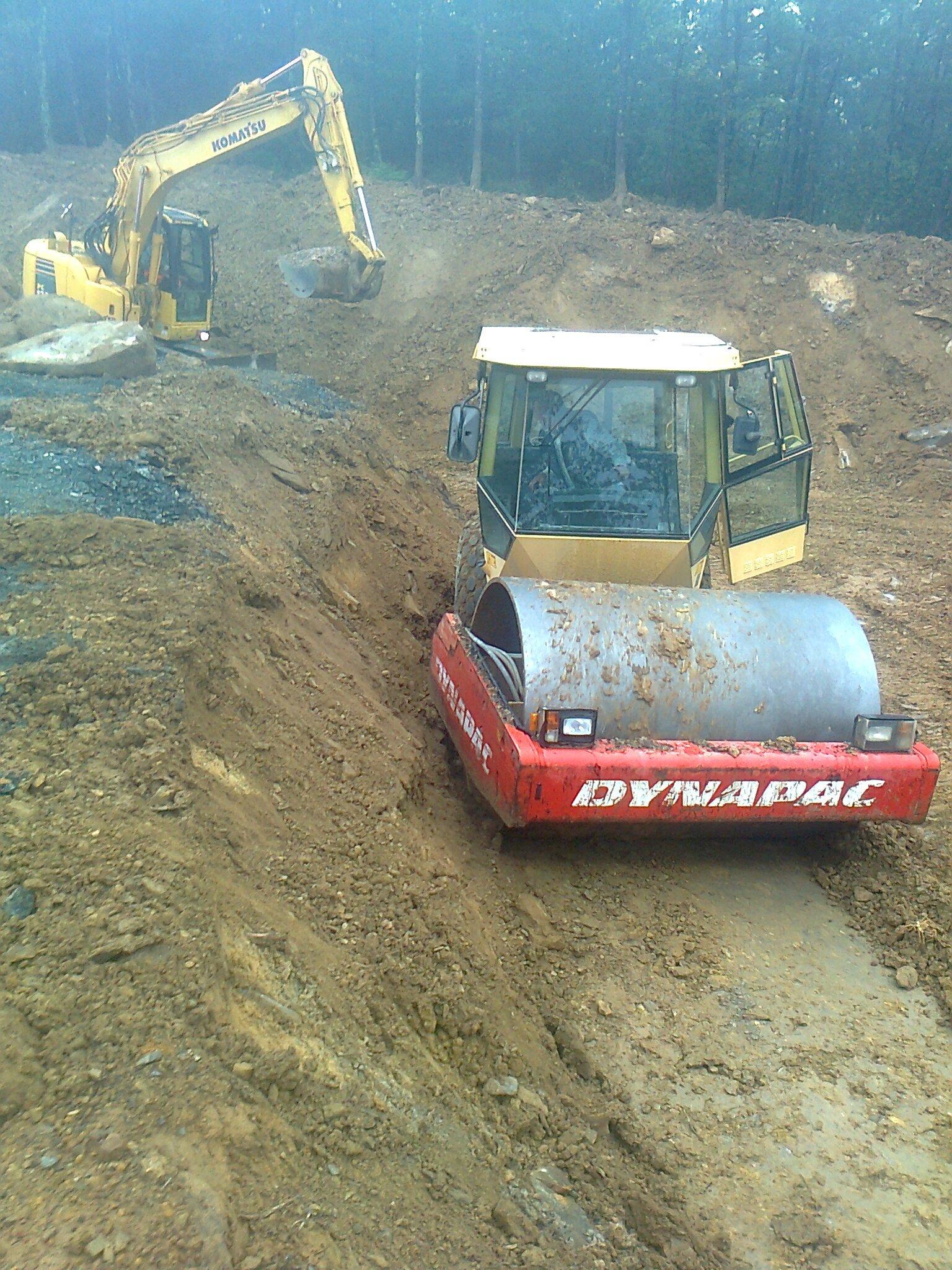 una scavatrice e una macchina per asfaltazione in un cantiere di terra